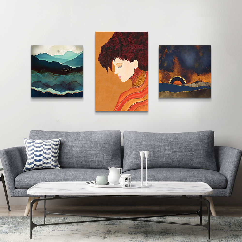Grey living room with three canvas prints: Indigo Mountains by SpaceFrog Designs, Anne by Viviana Gonzalez, and Before the Storm by SpaceFrog Designs