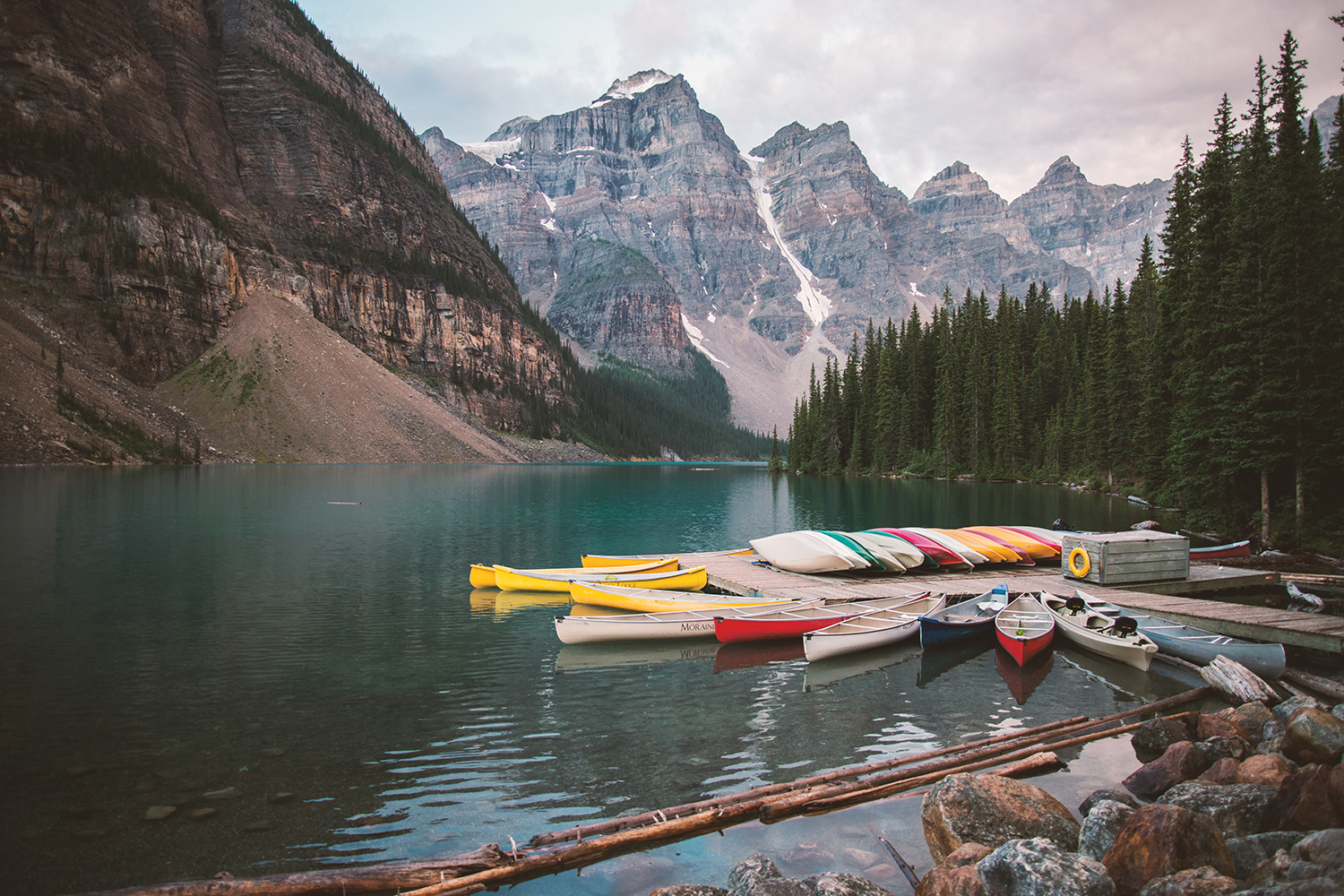 colorful canoes near a dock on a lake with mountains and trees in view
