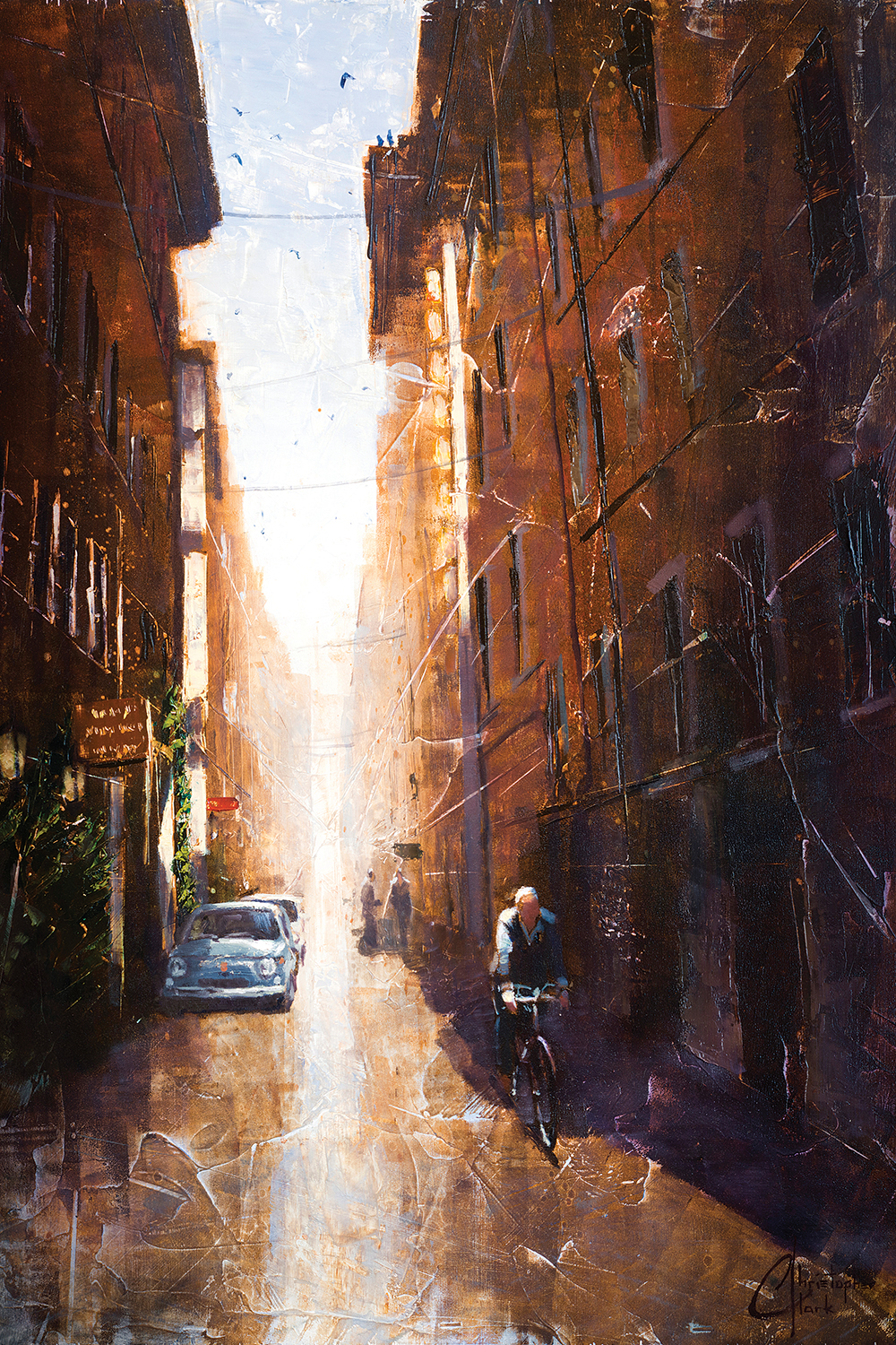 a small alley with some parked cars, a man bicycling, and some people in view with the sun bathing the alley