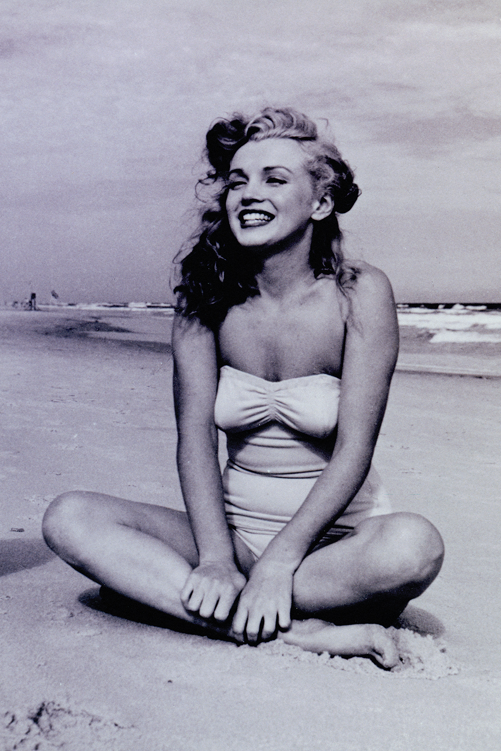 black and white picture of marilyn monroe sitting cross-legged and smiling on the beach