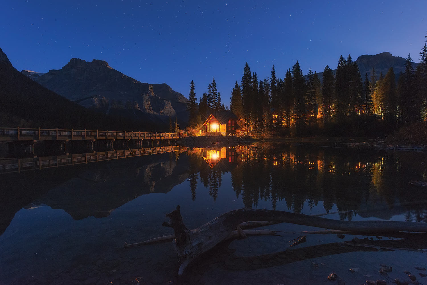 a small cabin on the lake with light on with woods and cabin reflected in water and stars seen in the sky