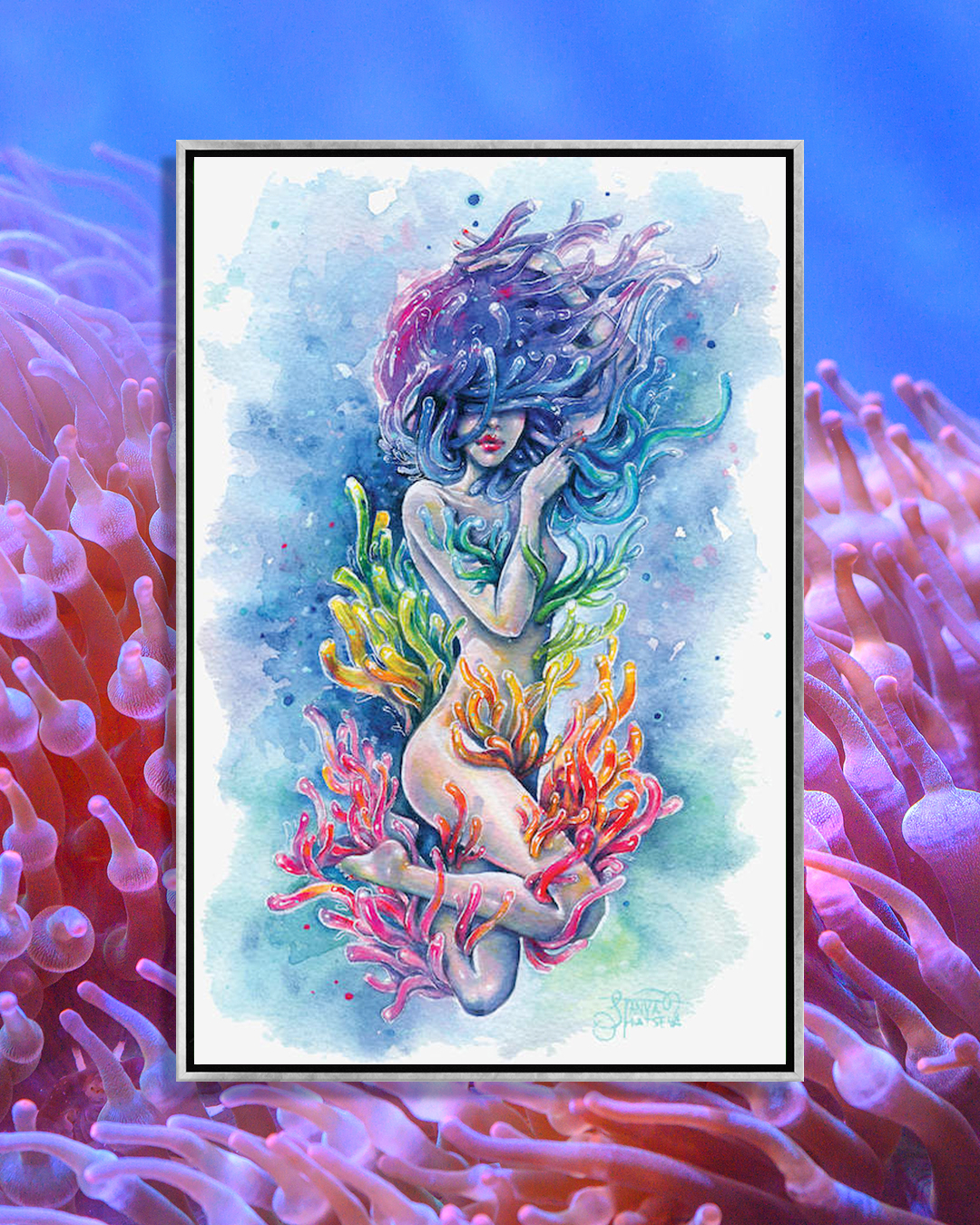 woman in water surrounded by rainbow coral including her hair