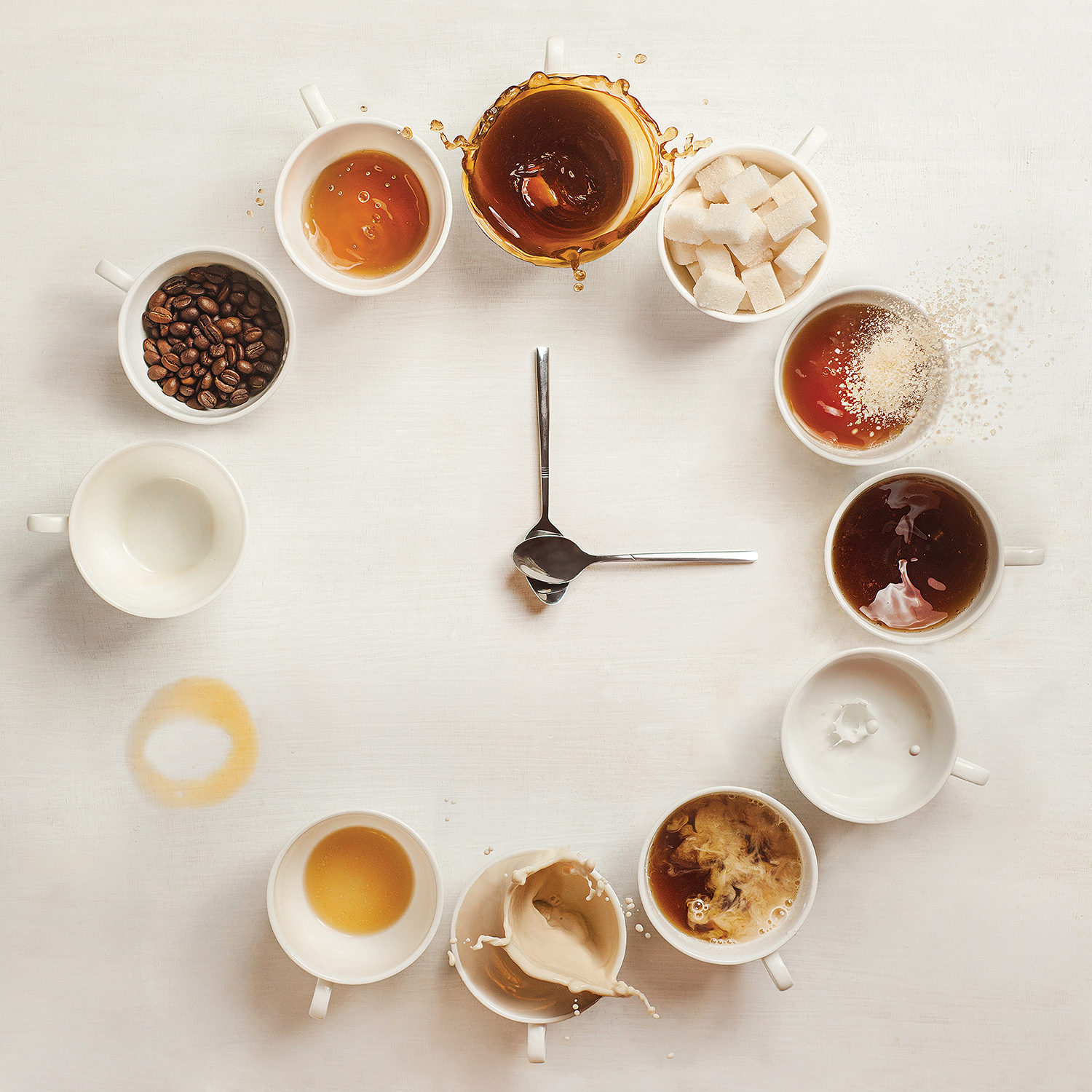 two spoons positioned like clock hands in the middle of a circle made of mugs with various coffee types