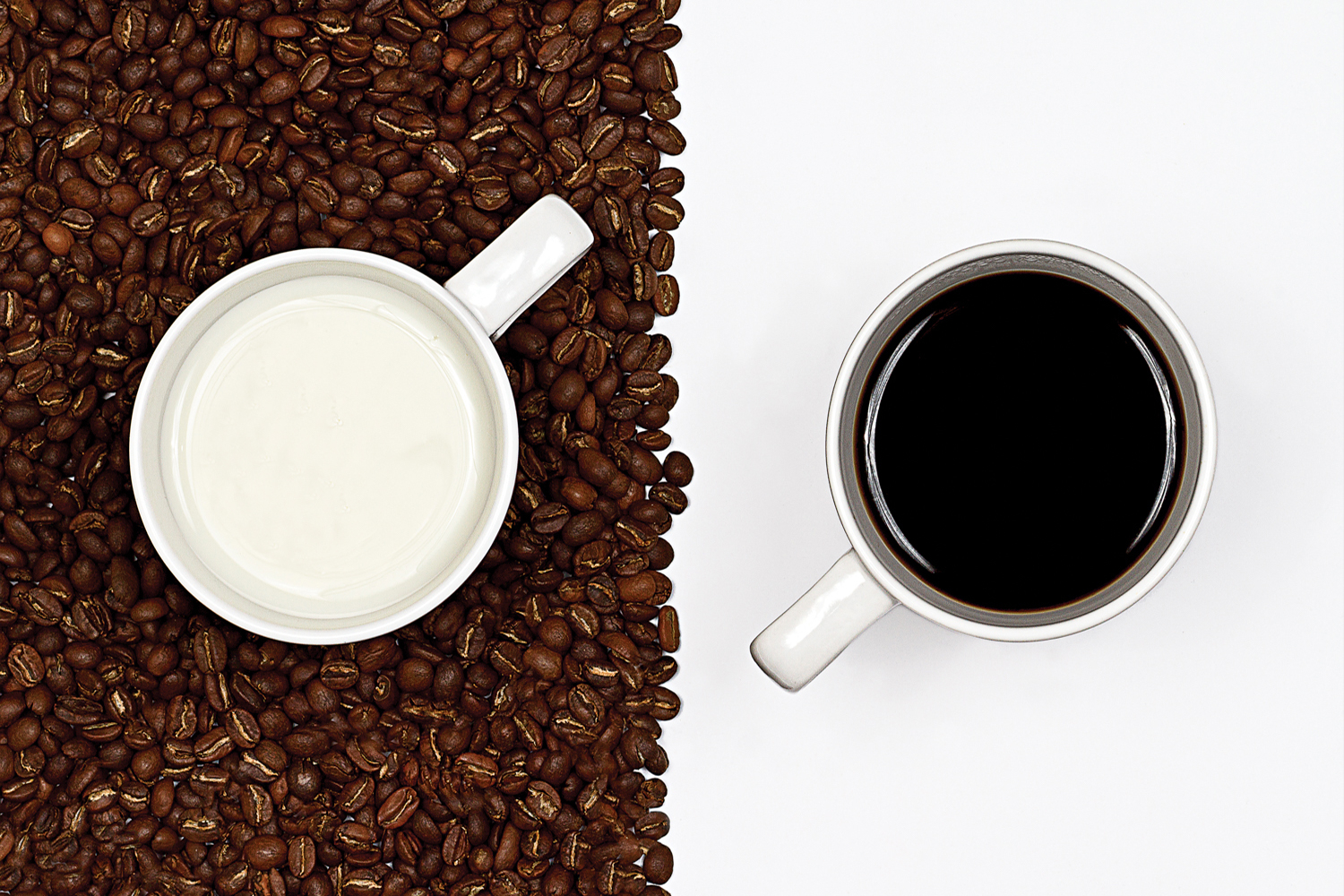 aerial view of two white mugs, one full of milk sitting on brown coffee beans and the other full of black coffee sitting on white