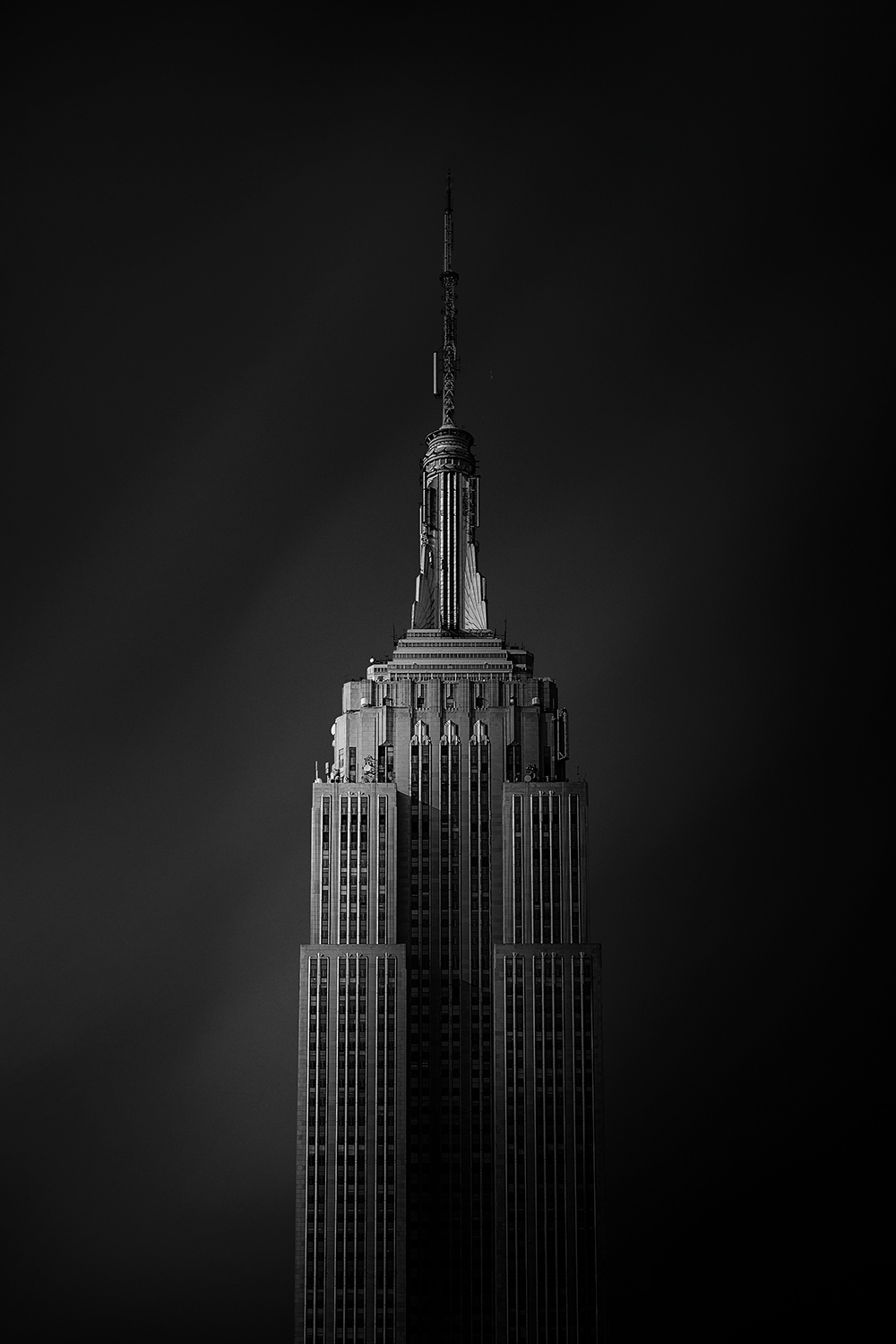 a black and white photograph showing the top of the empire state building in new york