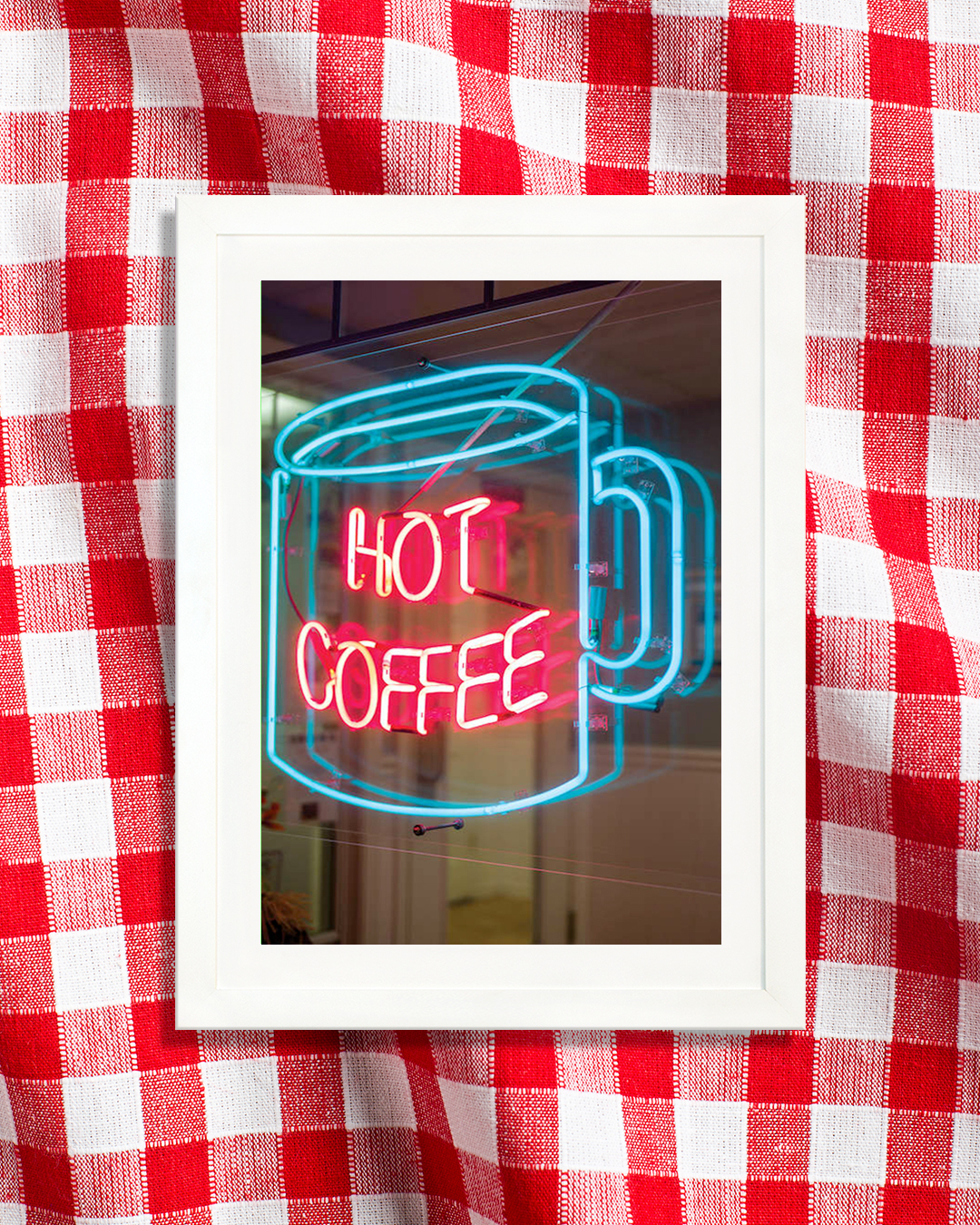 "a neon sign in a window showing a blue mug with the words ""hot coffee"" in red"