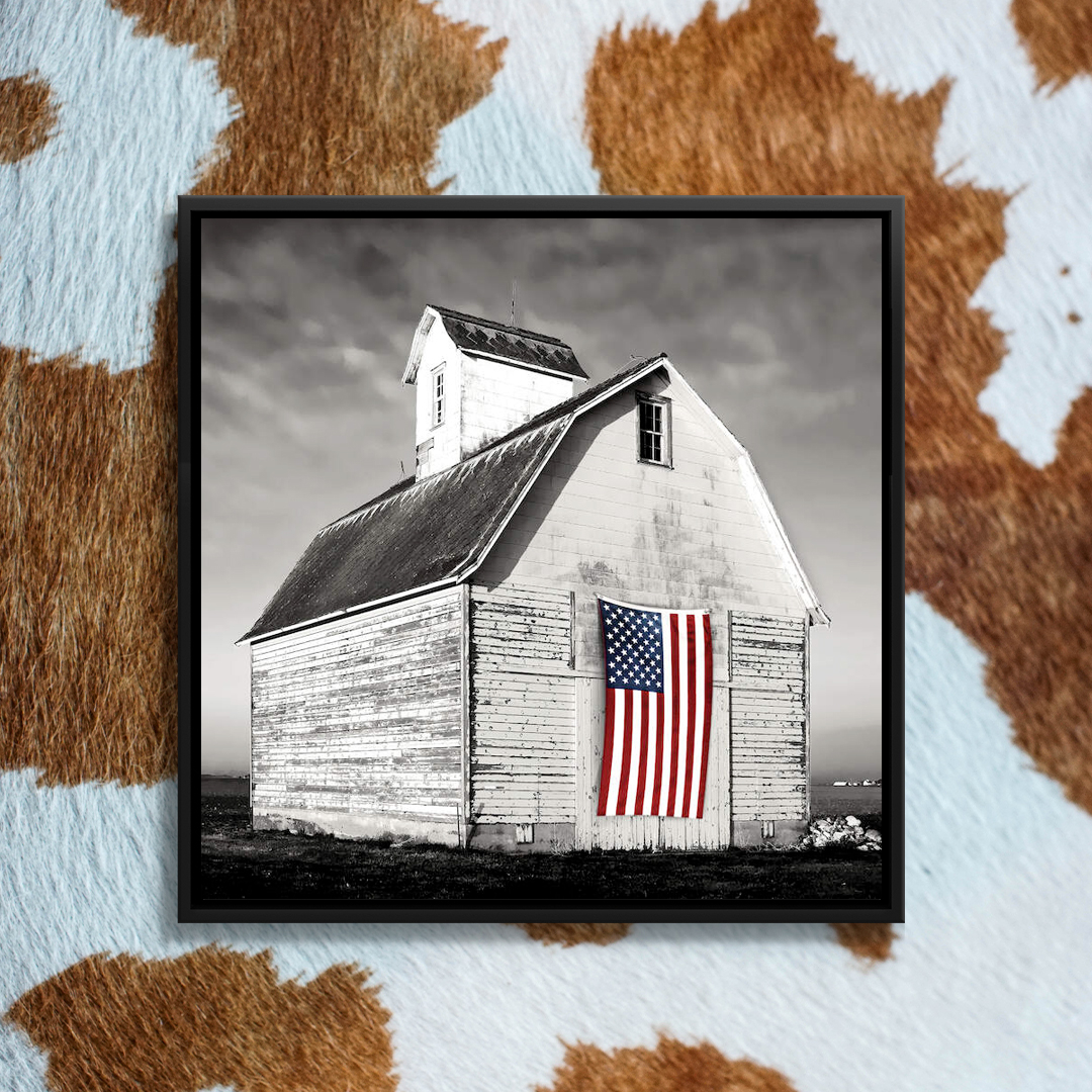 Black and white photo of a white barn with an American flag on the front door
