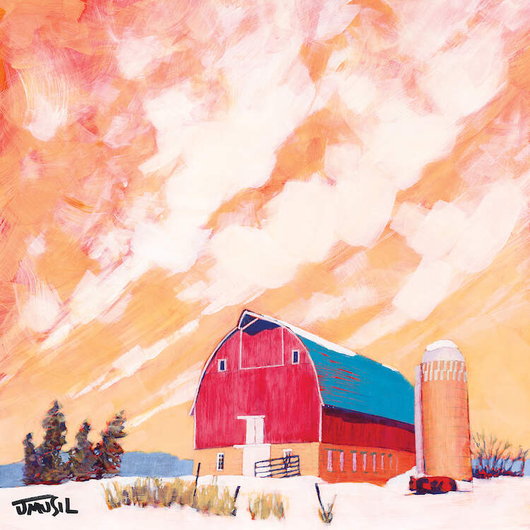 Red barn with blue roof on a large field under a yellow and orange sky with clouds