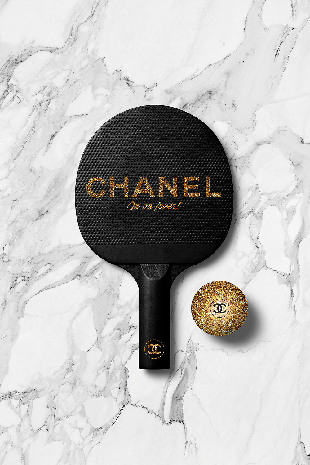 Black ping pong paddle with Chanel logo on it next to a gold Chanel ping pong ball on a white marble surface