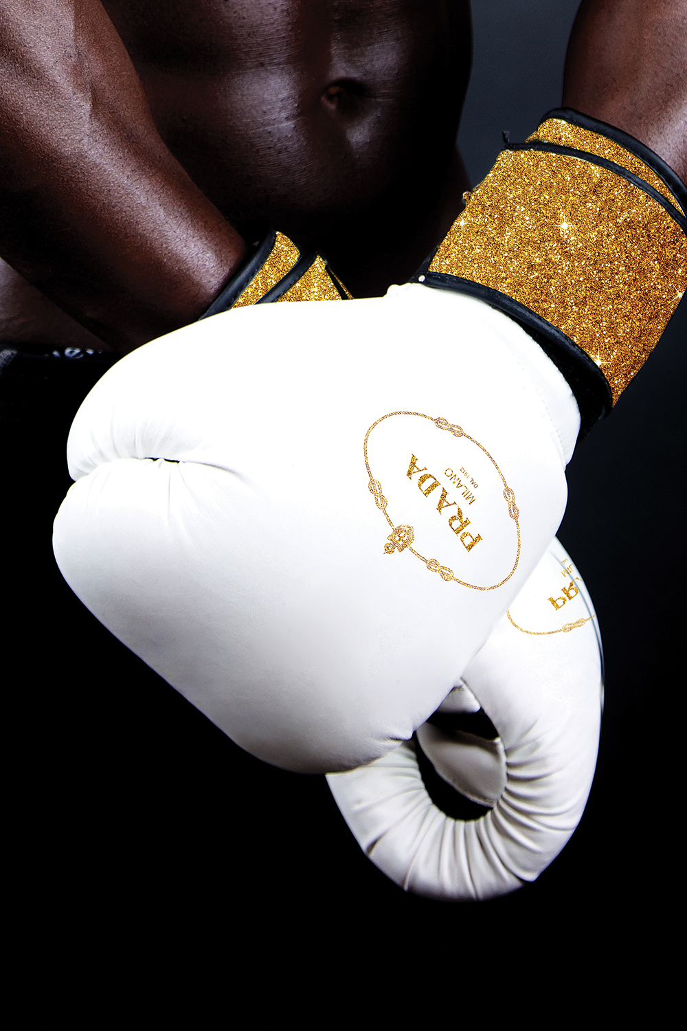 Photo of a black man with crossed arms wearing white boxing gloves with gold trim and a Prada logo