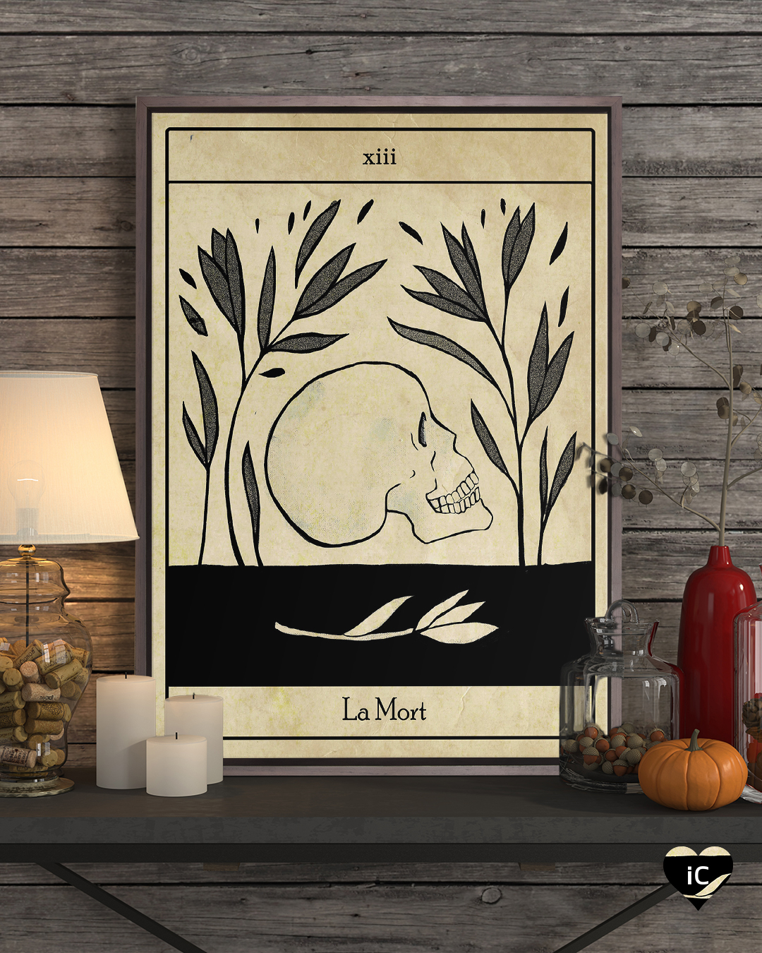 "Graphic of a tarot-card like image of a skull with text that says ""La Mort"" framed on a shelf with pumpkins, candles and vases"