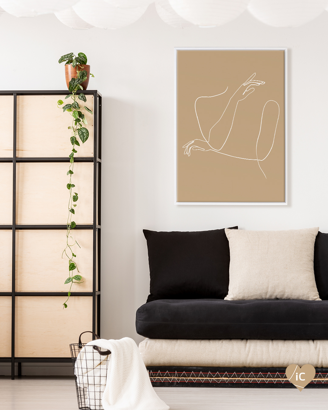 Tan colored graphic with figure-shaped white line drawing framed in white in a room with black and white sofa cushions and dresser with long ivy plant