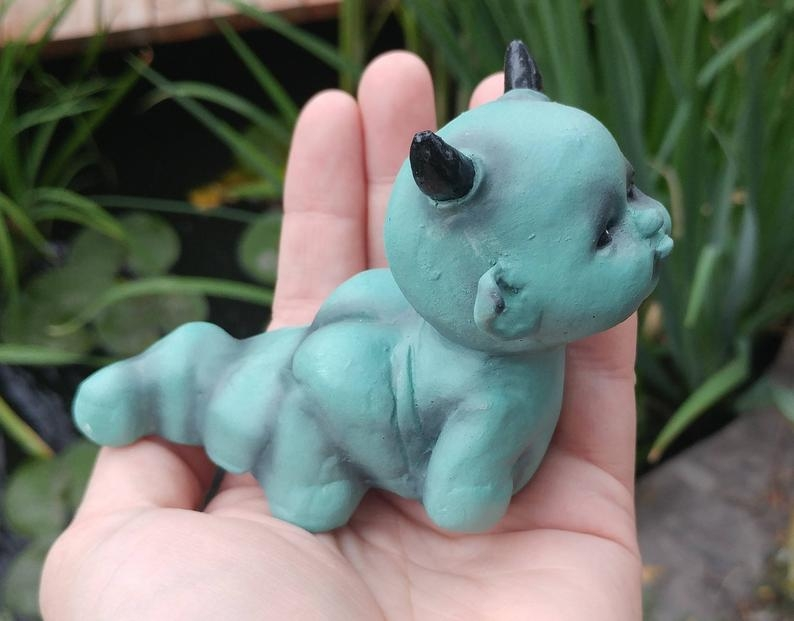 Teal colored figurine of baby demon grub with horns
