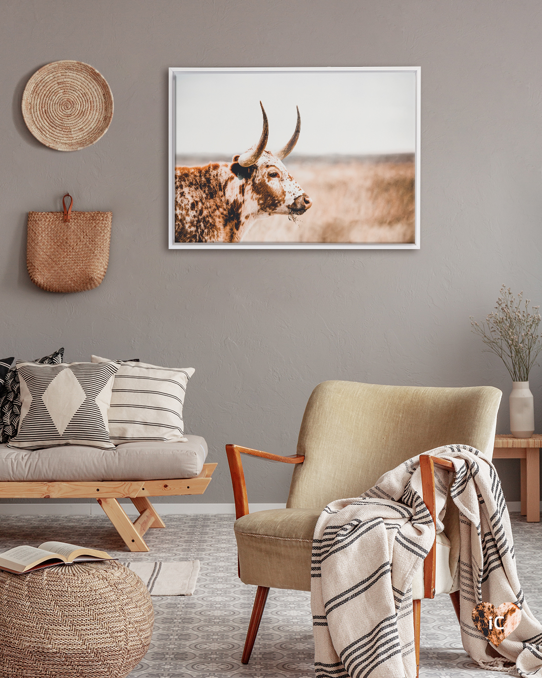 Photo of profile of a brown longhorn cow framed in white on a gray wall in room with wood furniture and white and beige accents