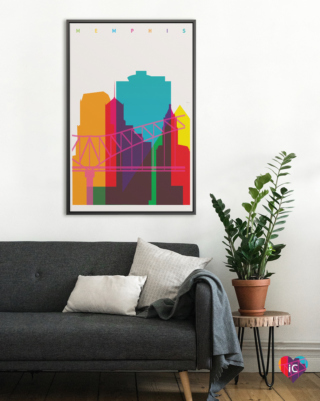 Minimalist graphic of outline of Memphis skyline and bridge in multiple colors on a beige background hanging on a wall in a living room with a black couch and potted plant