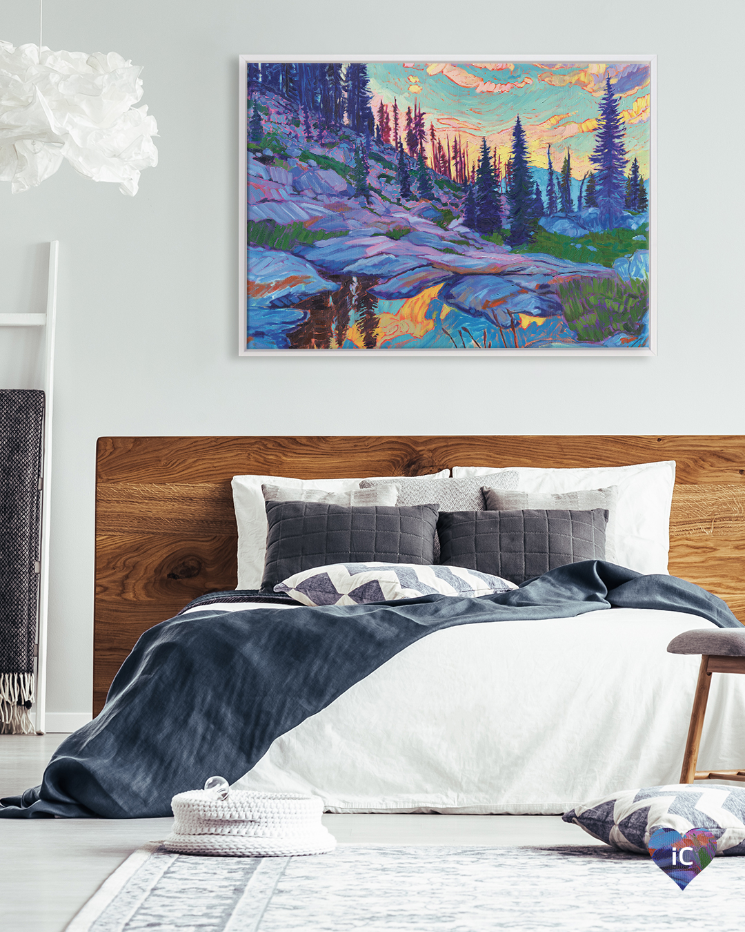 Colorful mountain landscape under sunset with tall trees framed in white in a bedroom with white bed and wood bedframe