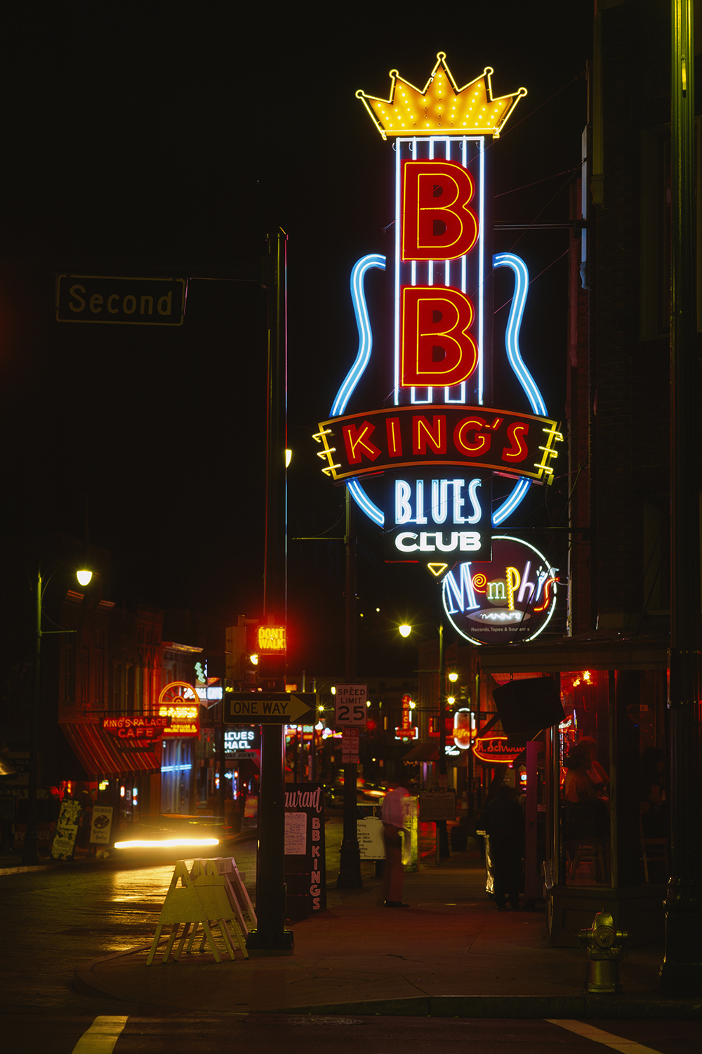 Photo of street in Memphis at night lit up by a neon sign of BB King's Blues Club