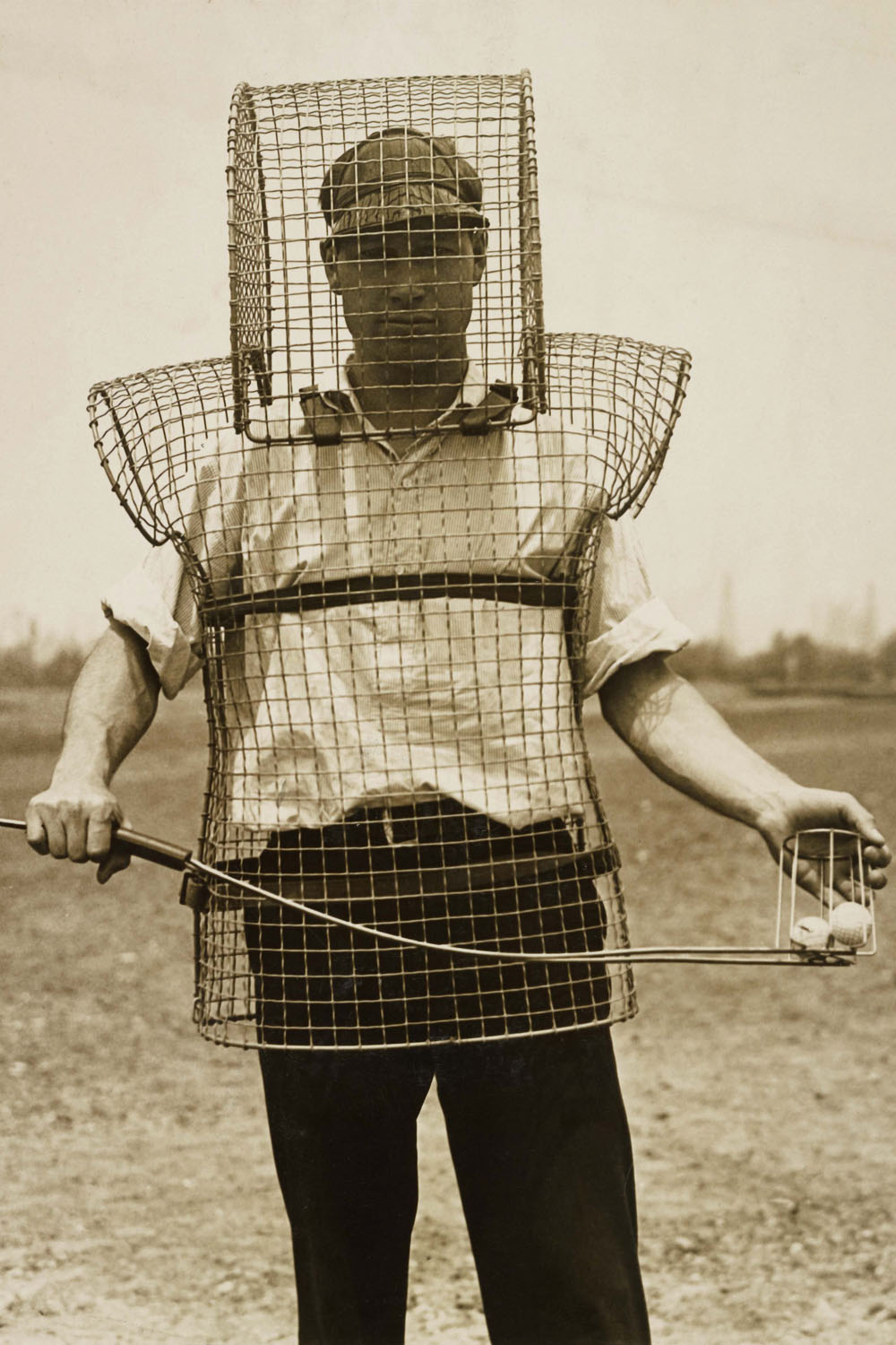 a man wearing a vintage cage-like solution for protection from golf balls