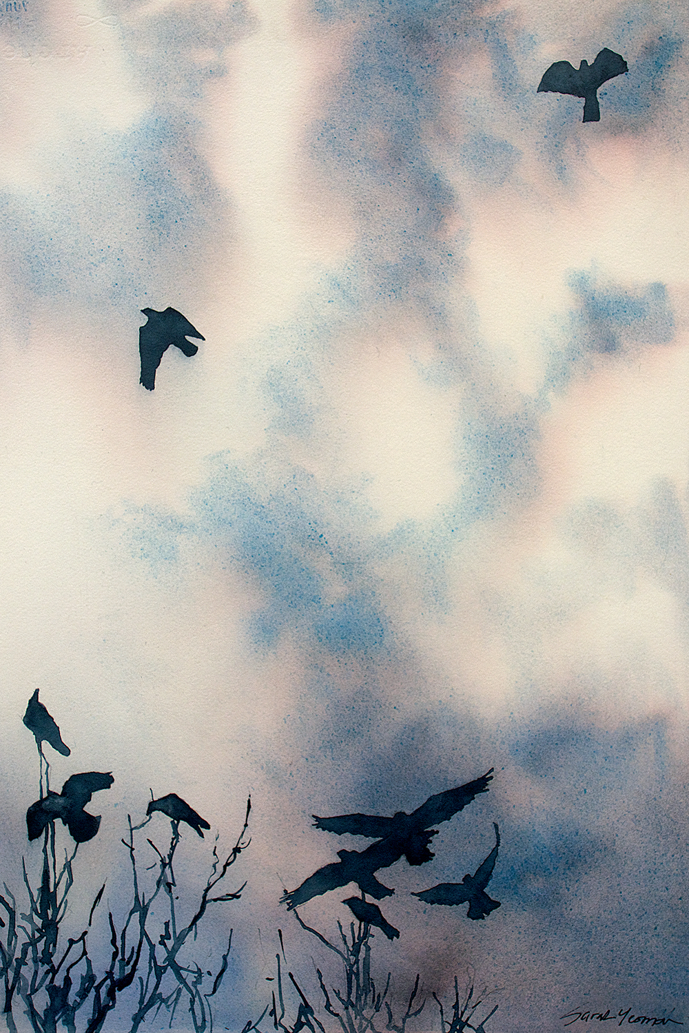 Crows flying in clouds over tops of dead tree branches