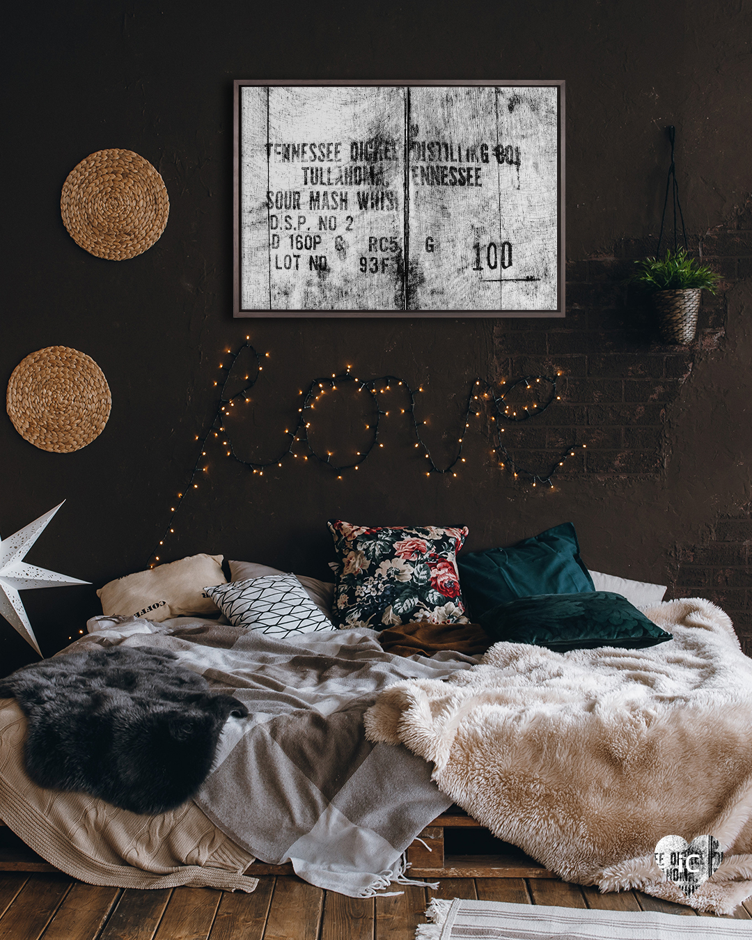Rustic wood engraving-inspired graphic of Tennessee whiskey distilling label framed on a brown wall in a bedroom with string lights and a potted plant