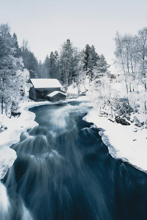 a black wood cabin next to a river surrounded by woods covered in snow