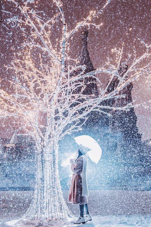 a woman standing under a clear umbrella while looking at an all white tree with white lights on it while it's snowing