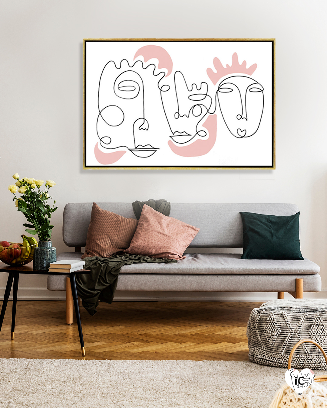 Minimalist line illustration of three portraits with pink shapes around them in a gold frame on a wall in a room with a gray couch and pink and green throw pillows