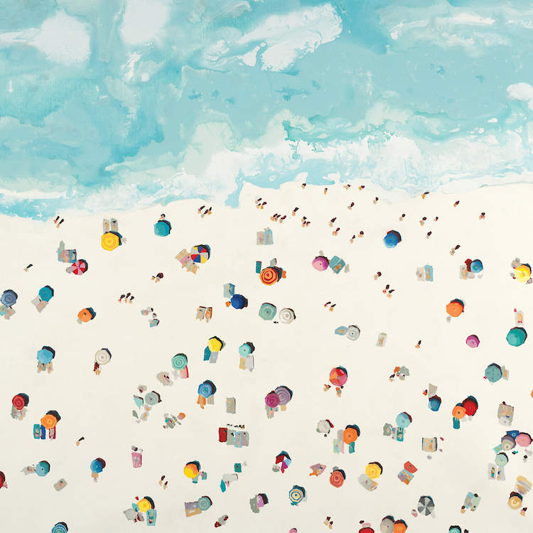 Aerial view of a group of colorful people and umbrellas on a beach near the waves