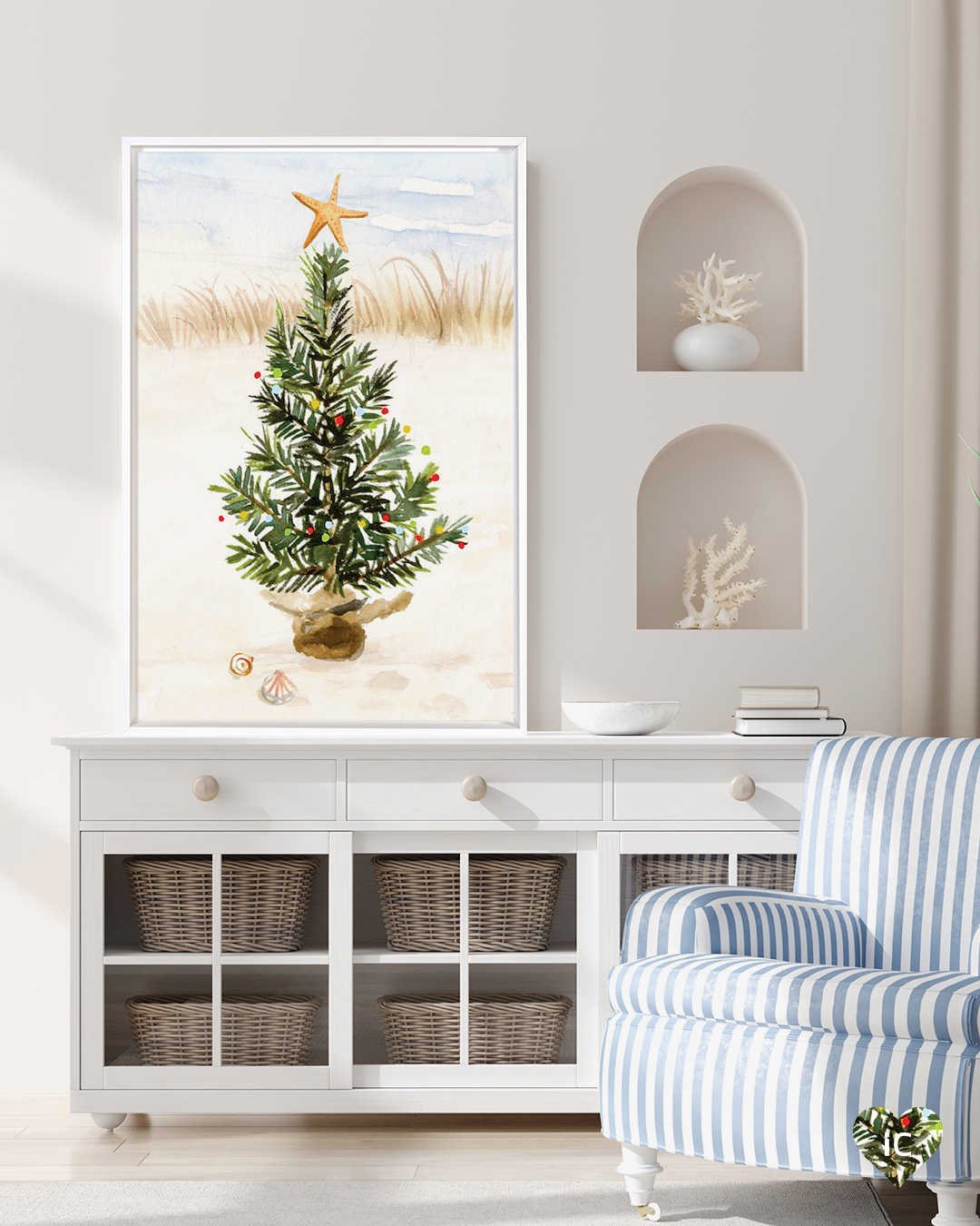 Print of a Christmas tree on a beach leaning on a white dresser in a coastal room with a blue and white arm chair