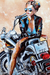 Female in sunglasses and leather jacket sitting on a motorcycle