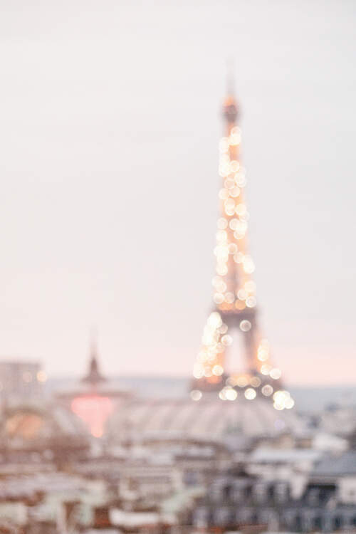 Bokeh photo of the Eiffel Tower with lights sparkling over Paris