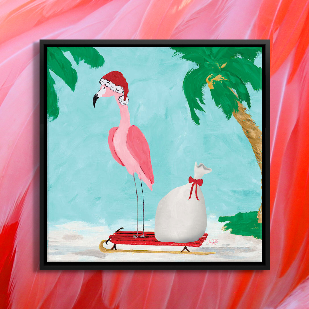 Pink flamingo wearing a Santa hat standing on a red sled on the beach
