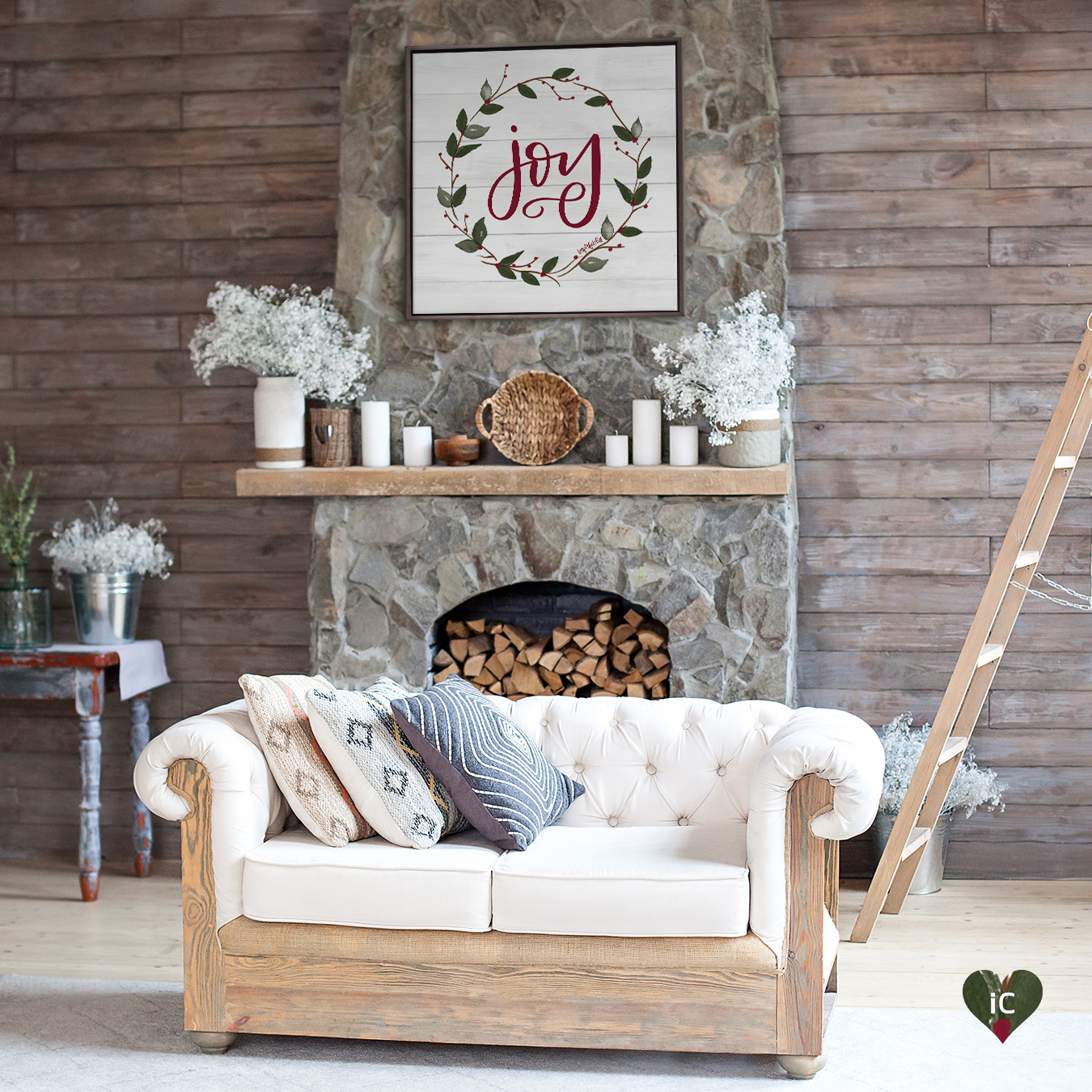 "White shiplap sign that says ""Joy"" in red text with a wreath around it hanging on a stone fireplace with logs piled in it, white candles stacked on the mantle, and a white love seat near it"