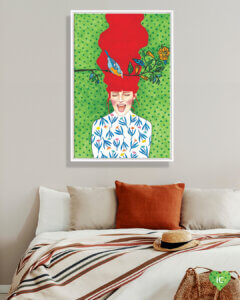 Image of a woman with red flowing hair yelling with eyes closed on a green background next to a tree branch with a bird on it, framed in white in a bedroom with an orange throw pillow