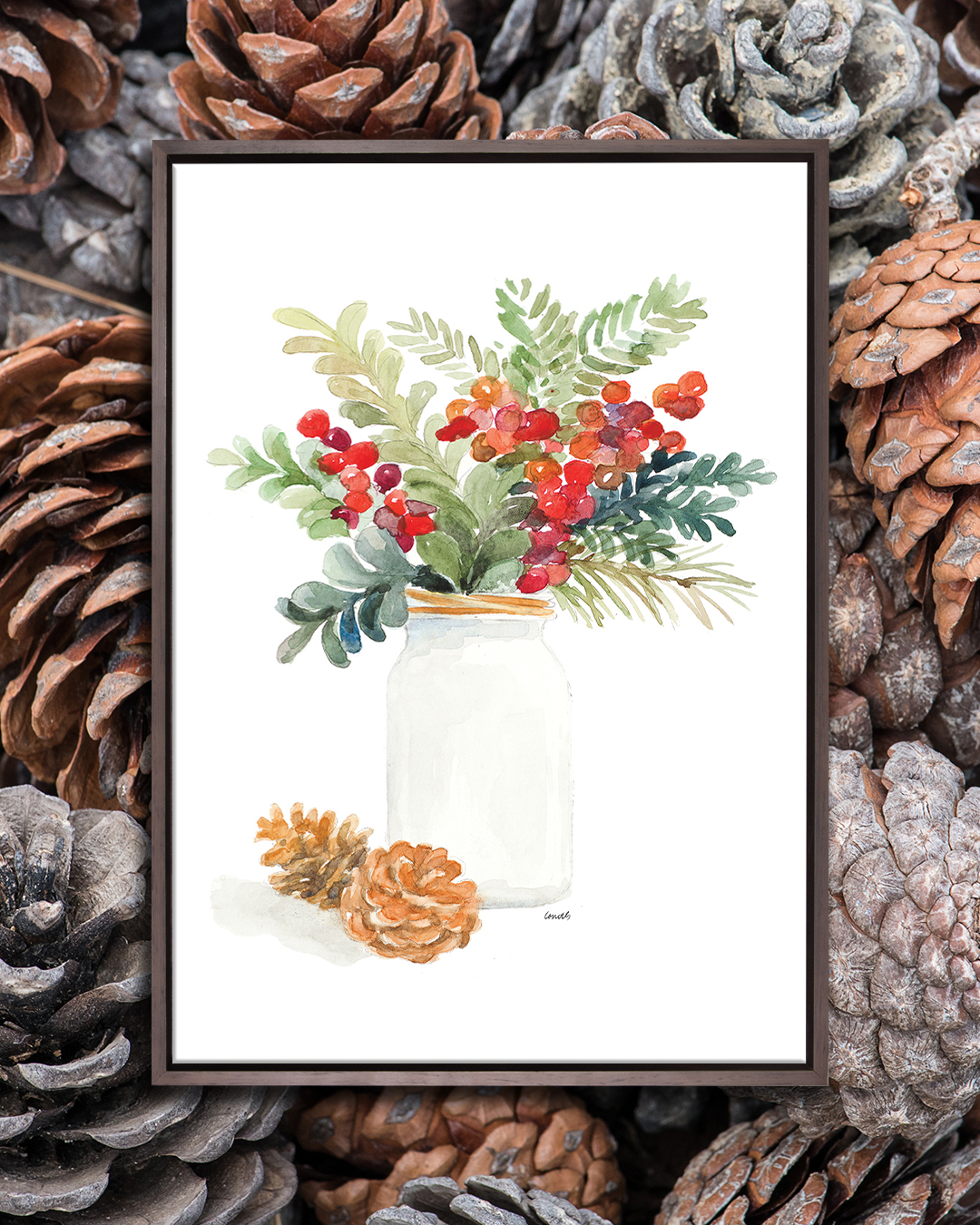White mason jar with holly and mistletoe in it near to two pine cones on a white background with a dark wood frame