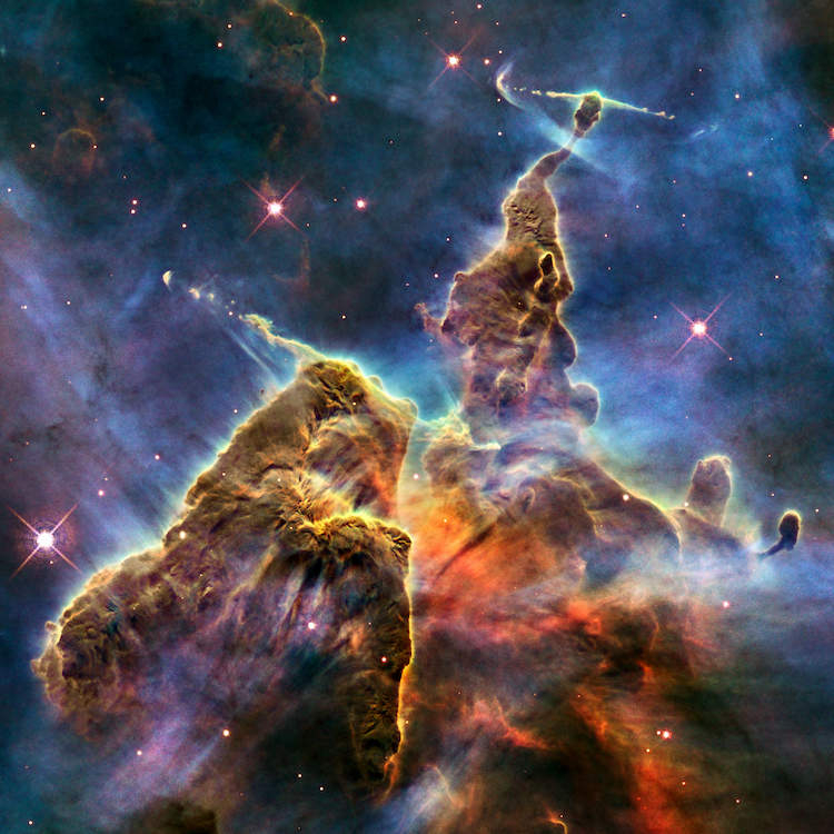 Photograph of a colorful mountain shaped nebula in space