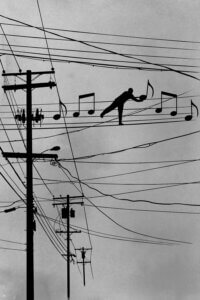 Graphic of a telephone pole with a man putting music notes on the wire