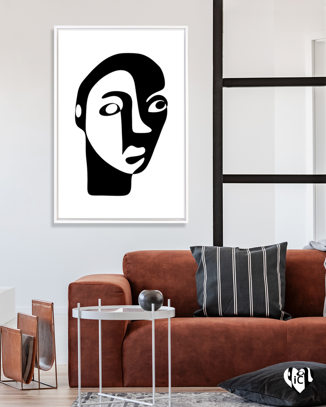 Minimalist portrait illustration of a shadowed face in a white frame on a wall in a room with a burgundy sofa and black and white striped throw pillow