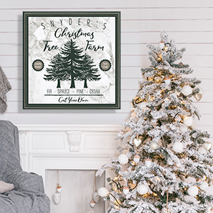 "Vintage sign that says ""Snyder's Christmas Tree Farm"" with green text hanging on a white shiplap wall over a fireplace in a room with a white and gold Christmas tree and a gray chair"