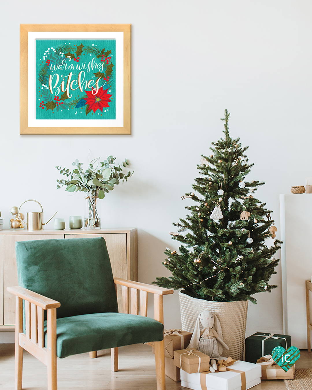 "Typography print with holiday elements that says ""Warm Wishes Bitches"" in a frame on a wall in a room with a mini Christmas tree and a green chair"