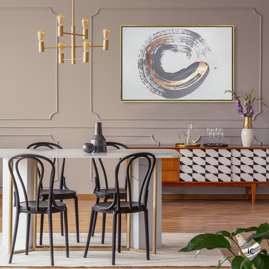 An abstract circular formation of brush strokes in a deep purple gray and metallic gold on a white background, framed in gold on a wall in a dining room setting