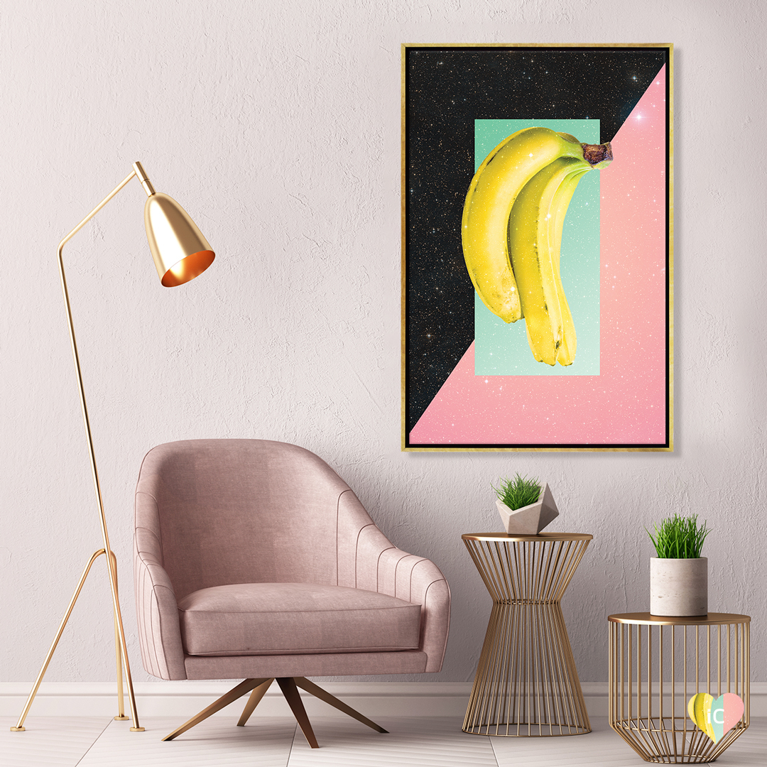 Two bananas over a pink and black sparkly background framed in gold hanging on a wall in a room with gold and pink deco style furniture
