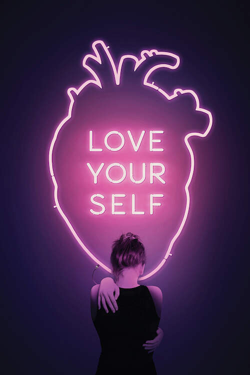 """Graphic of a pink neon outline of a human heart with text inside that says """"Love Your Self"""" with a female standing in front of it as she hugs herself"""