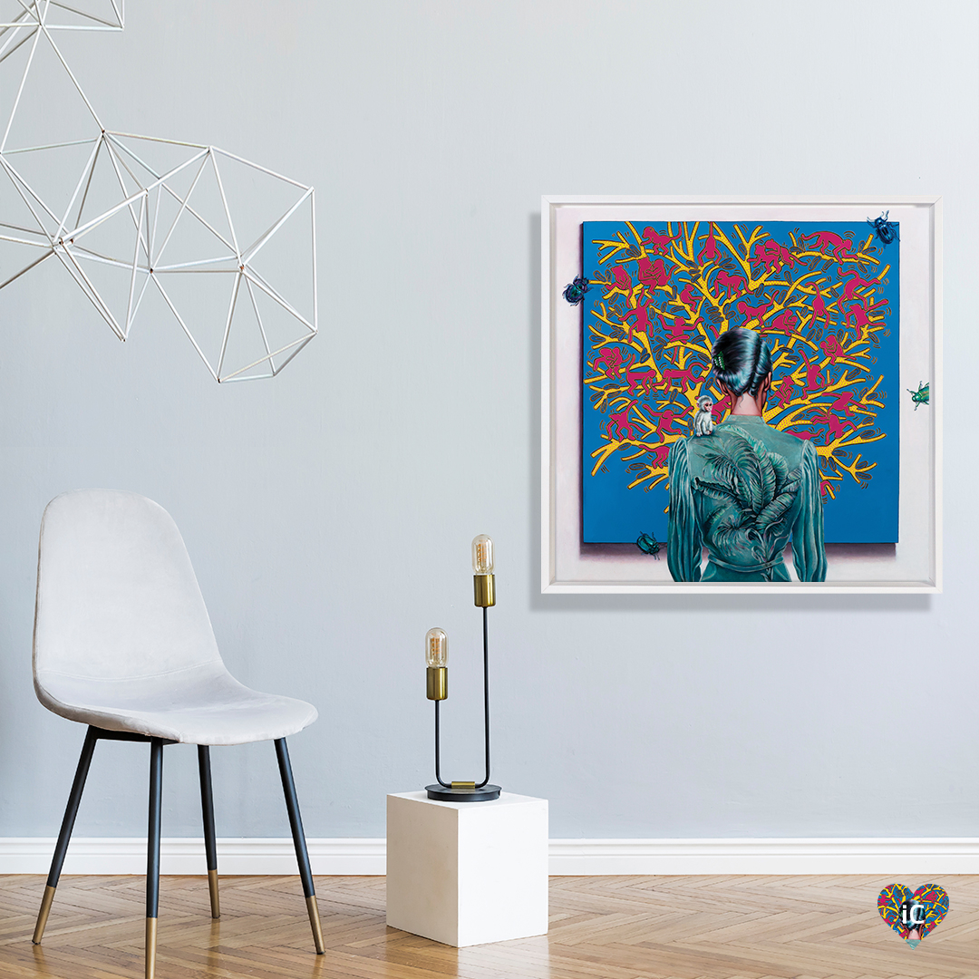 Backside view of woman looking at a piece of art in a gallery framed in white hanging on a wall in a white space with a chair and abstract art