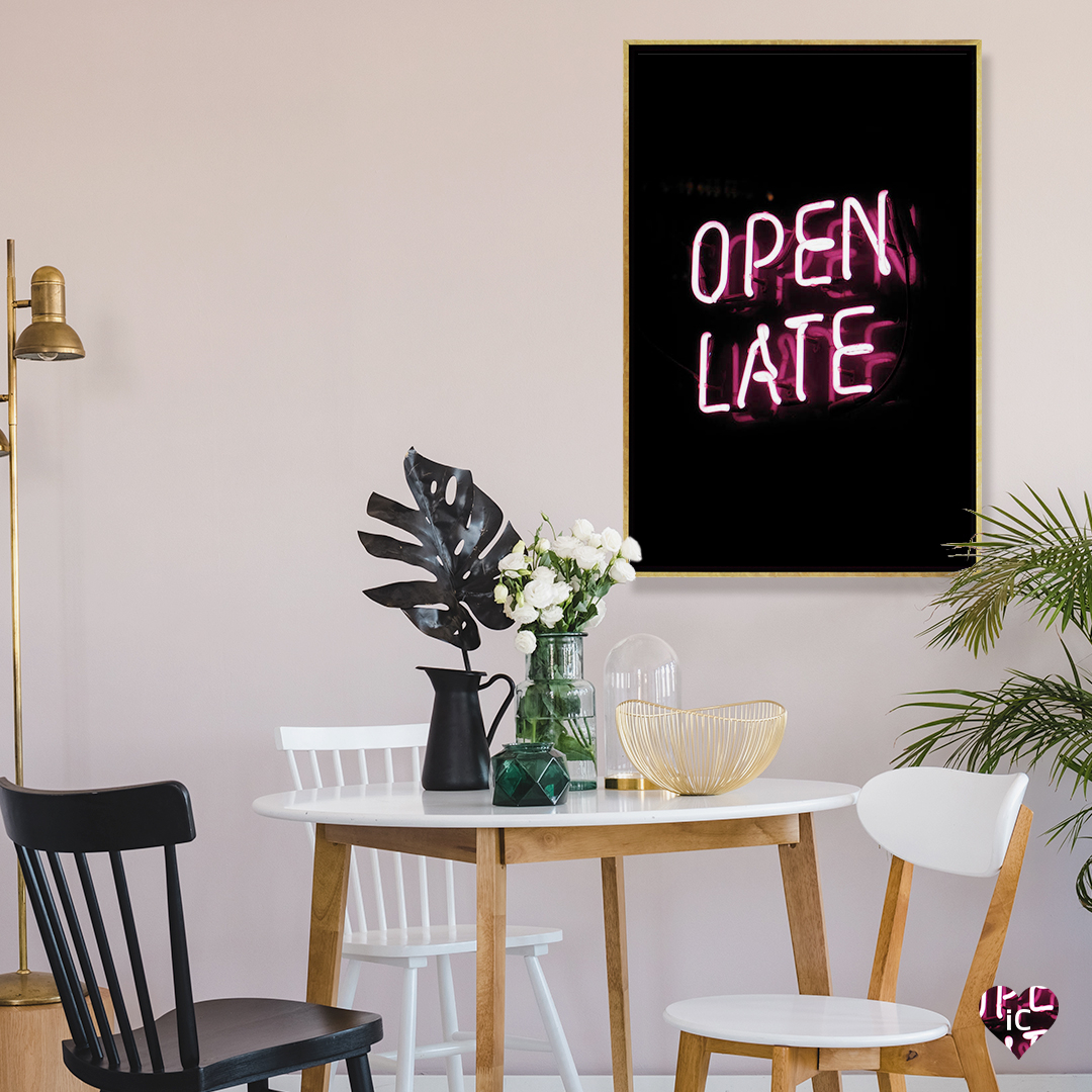 """Neon pink text that says """"Open Late"""" over a dark background, framed in gold on a wall in a dining room"""