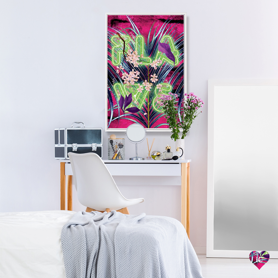 """Neon green text that says """"Flaws"""" over a pink, purple and blue tropical background, framed in white over a vanity table in a bedroom"""