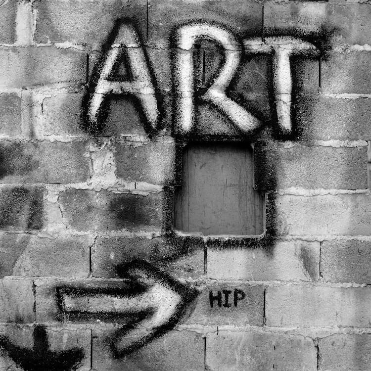 """Gray brick wall with word """"Art"""" and an arrow pointing to the word """"Hip"""" graffitied on it"""