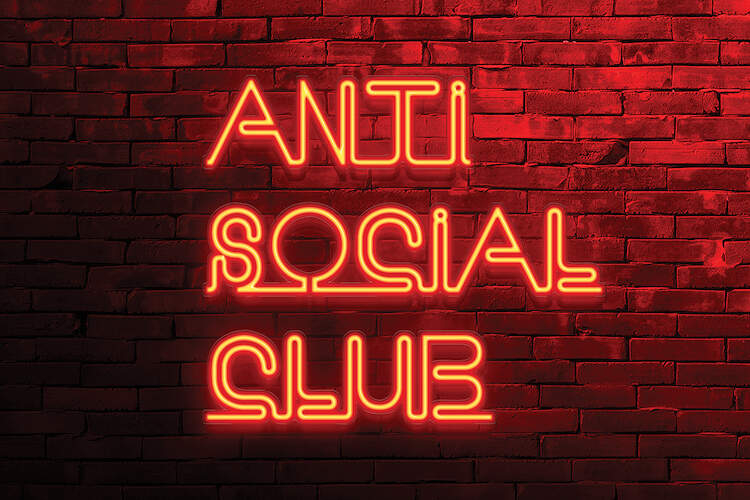 """Image of a red brick wall with a neon text sign in red letters that says """"Anti Social Club"""""""