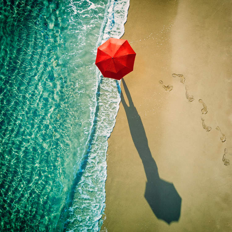 """""""Deep Water"""" by Ambra shows an aerial view of a person holding a red umbrella while walking down a sandy beach along the water's edge and their elongated shadow."""