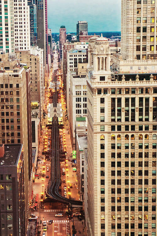 """""""City View"""" by Bill Carson Photography shows an aerial view of a busy city street surrounded by towering skyscrapers with a train line seen above the road."""
